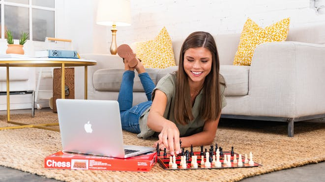Girl on the floor playing chess