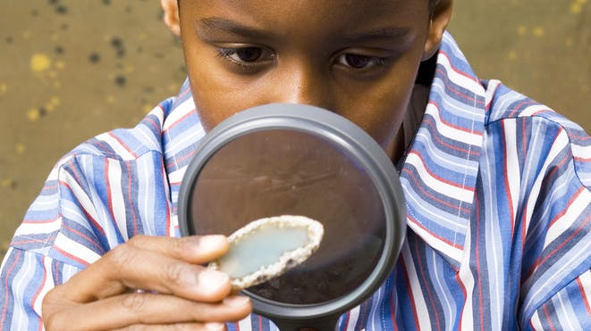 Boy looking at geode through a magnifying glass