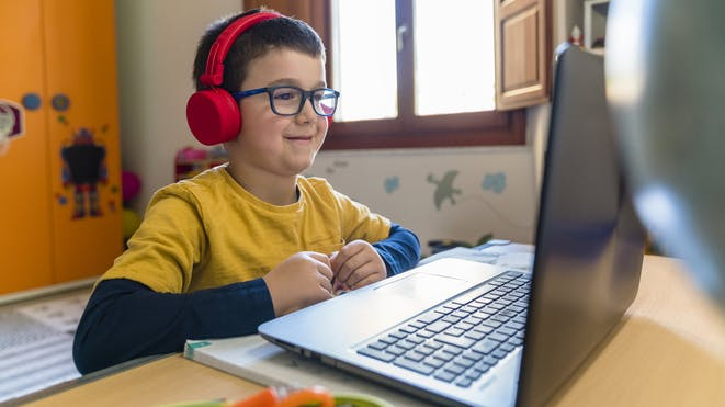 Boy playing on laptop with headphones