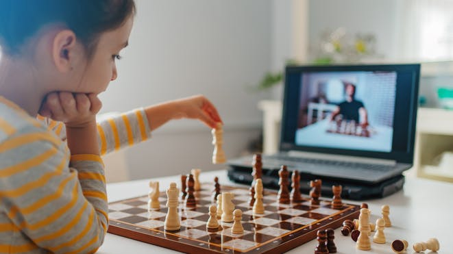 Child playing chess while watching tutorial on computer