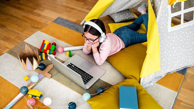 Girl in playroom watching class on laptop