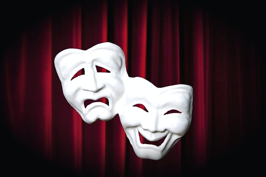 Comedy - tragedy masks in front of a red curtain