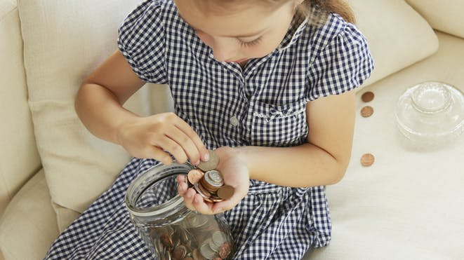 Child counting coins in glass jar