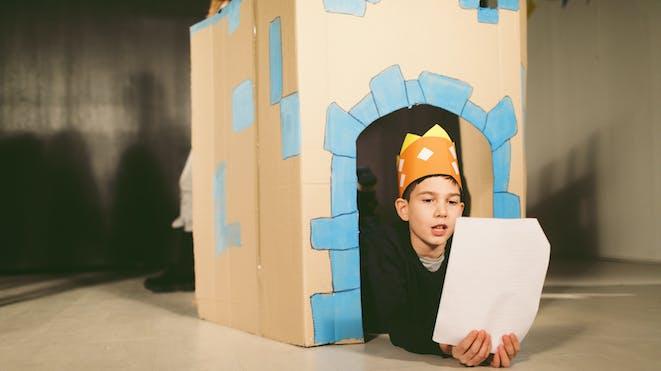 Boy reading lines inside cardboard set